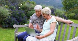 Couples supérieurs parlant et à l'aide de l'ordinateur portable sur le banc clips vidéos