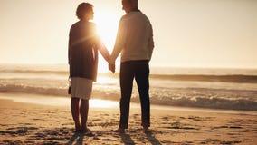 Couples supérieurs passant une certaine heure sur la plage au coucher du soleil Photographie stock libre de droits