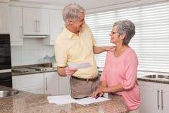 Couples supérieurs payant leurs factures Photographie stock