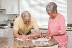 Couples supérieurs payant leurs factures Images stock