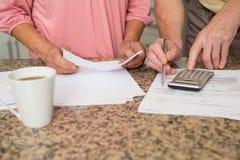Couples supérieurs payant leurs factures Image stock