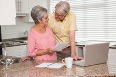 Couples supérieurs payant leurs factures avec l'ordinateur portable Photos stock