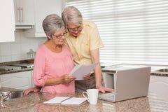 Couples supérieurs payant leurs factures avec l'ordinateur portable Photographie stock