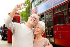Couples supérieurs photographiant sur la rue de ville de Londres Image libre de droits
