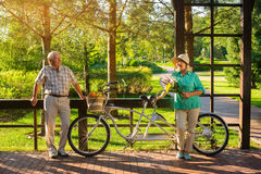 Couples supérieurs près de vélo tandem Photographie stock