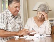 Couples supérieurs préoccupés par la dette passant par des factures ensemble Image stock
