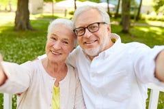 Couples supérieurs prenant le selfie au parc d'été Image libre de droits