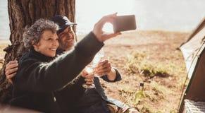Couples supérieurs prenant un selfie au lac Photo stock