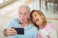 Couples supérieurs prenant un selfie au téléphone portable dans le salon photo stock