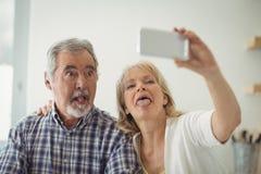 Couples supérieurs prenant un selfie dans la cuisine Images stock