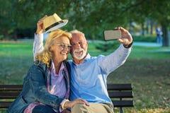 Couples supérieurs prenant une photo de selfie avec le téléphone intelligent en parc images stock