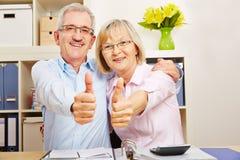 Couples supérieurs réussis tenant des pouces  Photos stock