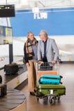 Couples supérieurs rassemblant des bagages de la bande de conveyeur à l'aéroport Photos stock