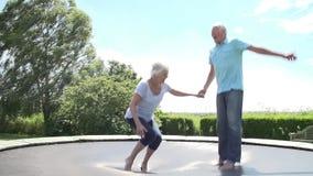 Couples supérieurs rebondissant sur le trempoline dans le mouvement lent banque de vidéos