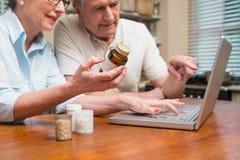 Couples supérieurs recherchant le médicament en ligne Photo stock