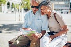 Couples supérieurs recherchant une destination sur une carte de ville Photos stock