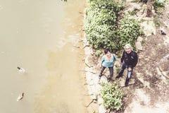Couples supérieurs regardant des canards nageant en rivière Neckar Photographie stock
