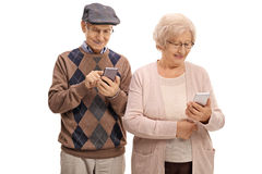 Couples supérieurs regardant des téléphones image stock