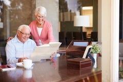 Couples supérieurs regardant l'album photos par la fenêtre Photos stock