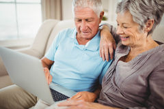 Couples supérieurs regardant l'ordinateur portable Image libre de droits