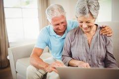 Couples supérieurs regardant l'ordinateur portable Photo stock