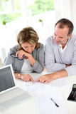 Couples supérieurs regardant le plan de construction Photographie stock libre de droits