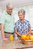 Couples supérieurs regardant le verre de jus d'orange Images libres de droits