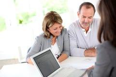 Couples supérieurs rencontrant l'agent immobilier Image stock