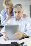 Couples supérieurs rendant une déclaration d'impôts en ligne image stock