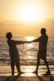 Couples supérieurs retenant la plage tropicale de coucher du soleil de mains Photos libres de droits
