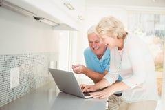 Couples supérieurs riant tout en à l'aide de l'ordinateur portable dans la cuisine Images libres de droits