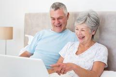 Couples supérieurs riant tout en à l'aide de l'ordinateur portable dans le lit Photo stock