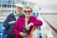 Couples supérieurs riants appréciant la plate-forme d'un bateau de croisière Images libres de droits