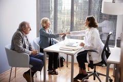 Couples supérieurs salué par visite femelle de docteur With Handshake On à l'hôpital pour la consultation photos stock