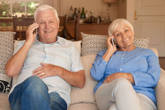 Couples supérieurs satisfaits se reposant et parlant sur des téléphones portables à la maison Photo libre de droits