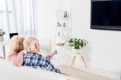 couples supérieurs se reposant au divan confortable et à la TV de observation photos libres de droits