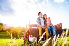 Couples supérieurs se reposant derrière le camion pick-up rouge Images stock