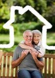Couples supérieurs se reposant en parc avec le contour à la maison photographie stock libre de droits