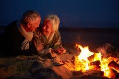 Couples supérieurs se reposant par le feu sur la plage d'hiver Image libre de droits