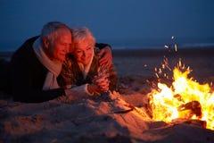 Couples supérieurs se reposant par le feu sur la plage d'hiver Photographie stock