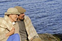 Couples supérieurs se reposant par un bord de lac avec la couverture autour des épaules Photos libres de droits