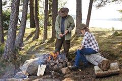 Couples supérieurs se reposant par un feu de camp près d'un lac Image libre de droits