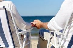 Couples supérieurs se reposant sur des chaises à la plage d'été Images libres de droits