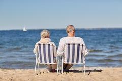 Couples supérieurs se reposant sur des chaises à la plage d'été Photo libre de droits