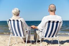 Couples supérieurs se reposant sur des chaises à la plage d'été Image stock