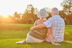 Couples supérieurs se reposant sur l'herbe Photographie stock libre de droits