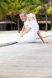 Couples supérieurs se reposant sur la jetée en bois Photo libre de droits