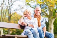 Couples supérieurs se reposant sur le banc de partie dans la chute Image stock