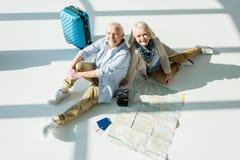Couples supérieurs se reposant sur le plancher avec le sac, la carte et les passeports de déplacement Photographie stock libre de droits