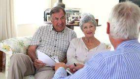 Couples supérieurs se reposant sur Sofa Talking To Financial Advisor banque de vidéos
